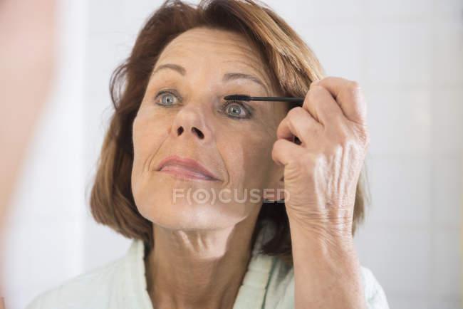 Femme âgée appliquant le mascara — Photo de stock