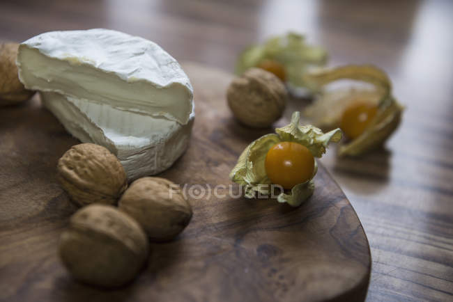 Two halves of cheese and walnuts — Stock Photo