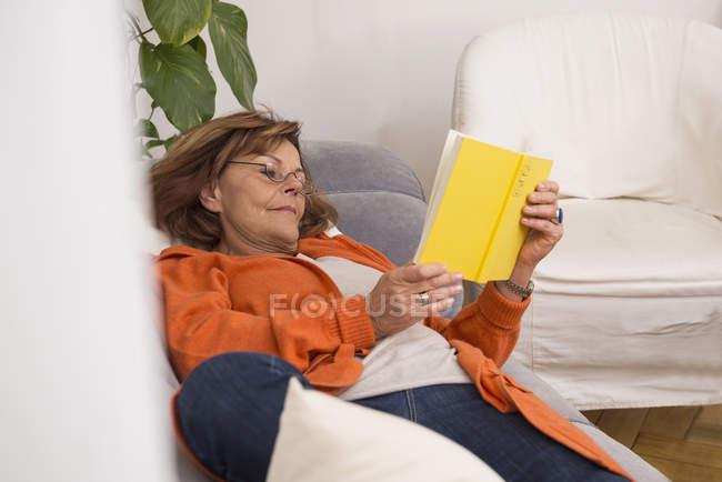 Mujer mayor leyendo un libro - foto de stock
