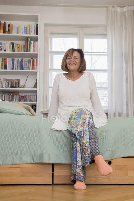 Senior woman sitting on bed and smiling — Stock Photo