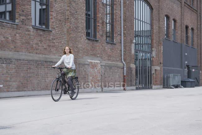 Молода жінка їде на велосипеді. — стокове фото