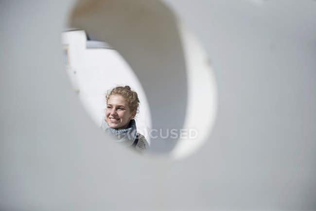 Mulher vista através de um buraco redondo — Fotografia de Stock