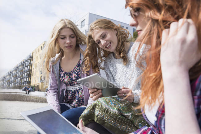 Three friends using digital tablet — Stock Photo