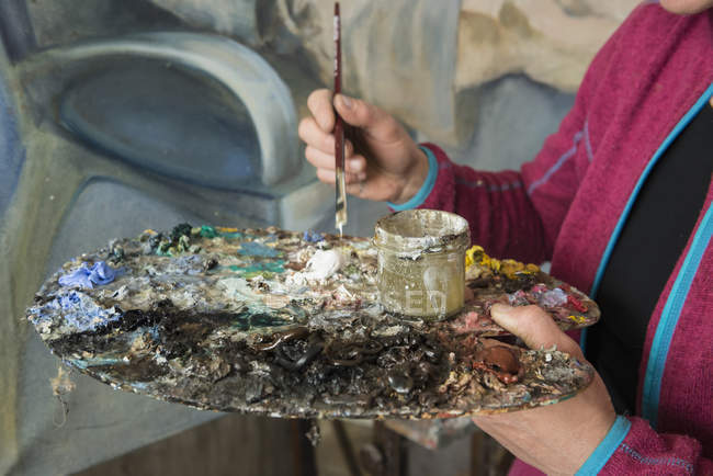 Woman mixing colors while painting — Stock Photo