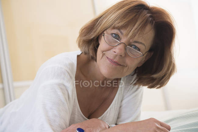 Senior woman lying on bed — Stock Photo