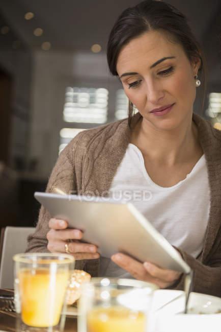 Женщина с помощью цифрового планшета на завтрак — стоковое фото