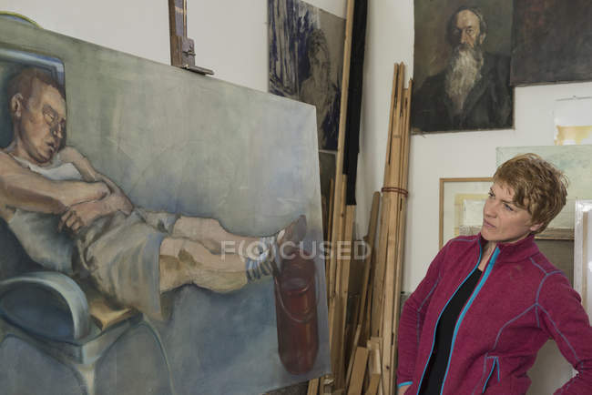 Female artist looking at painting on easel — Stock Photo