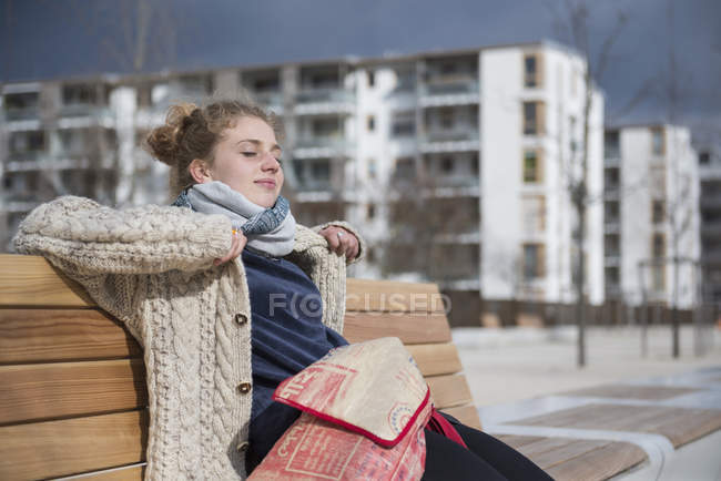 Young woman sitting on bench in city — Stock Photo