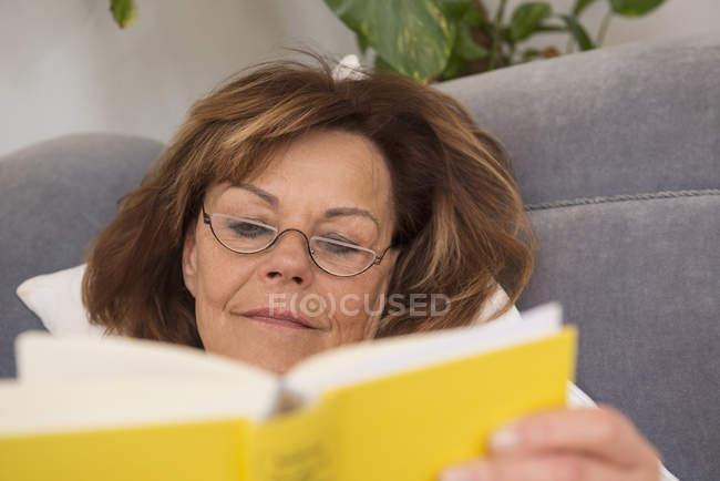 Старша жінка читає книжку. — стокове фото