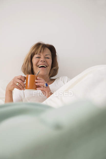 Senior woman at bedroom drinking tea — Stock Photo