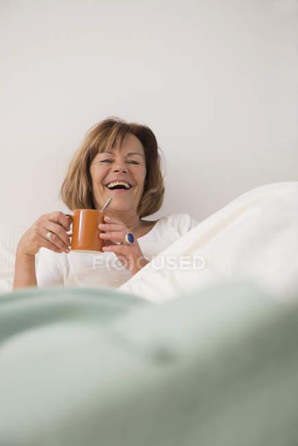 Старшая женщина в спальне пьет чай — стоковое фото