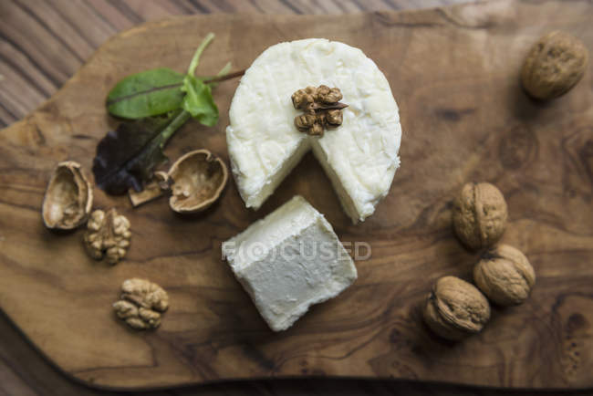 Cheese and walnuts on a chopping board — Stock Photo