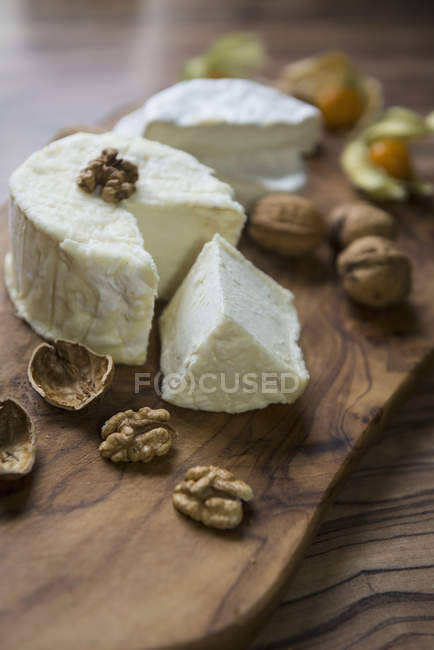 Cheese and walnuts on chopping board — Stock Photo
