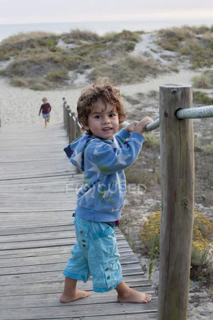 Маленький ребенок, стоящий на набережной — стоковое фото