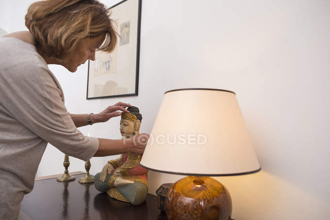 Senior woman touches Buddha statue — Stock Photo