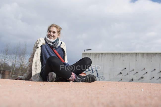 Молодая женщина сидит со скрещенными ногами — стоковое фото