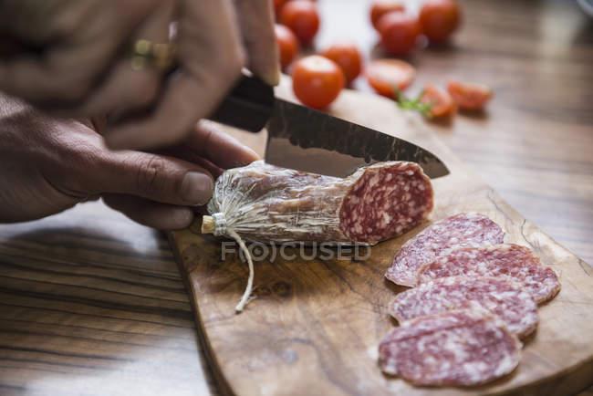 Mano de la persona para picar salchichas con cuchillo - foto de stock