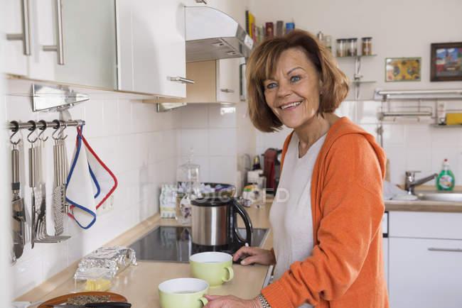 Donna anziana che prepara il tè in cucina — Foto stock