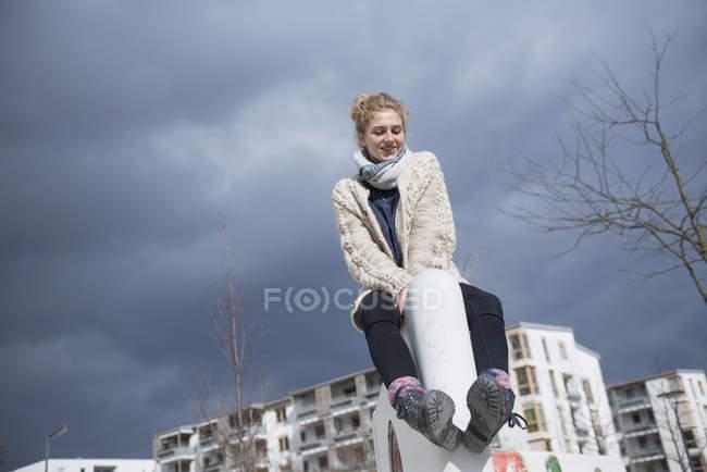 Jovem mulher sentada na parede — Fotografia de Stock