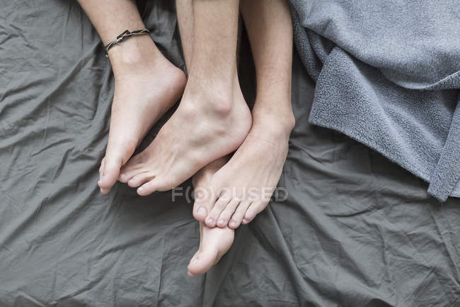 Homosexual couple legs in bed — Stock Photo