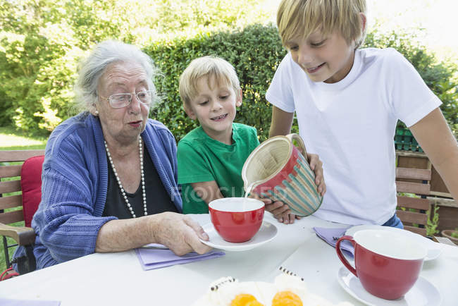 Grandson pouring milk in grandmothers cup — Stock Photo