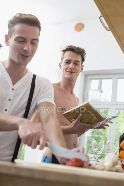 Homosexual couple cooking in the kitchen — Stock Photo