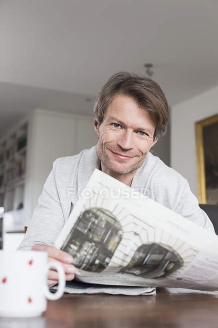 Man having coffee and reading newspaper — Stock Photo