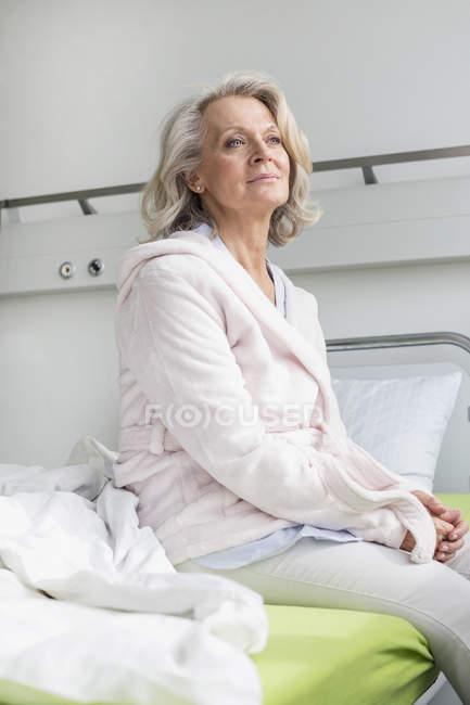 Paciente sentado en la cama - foto de stock