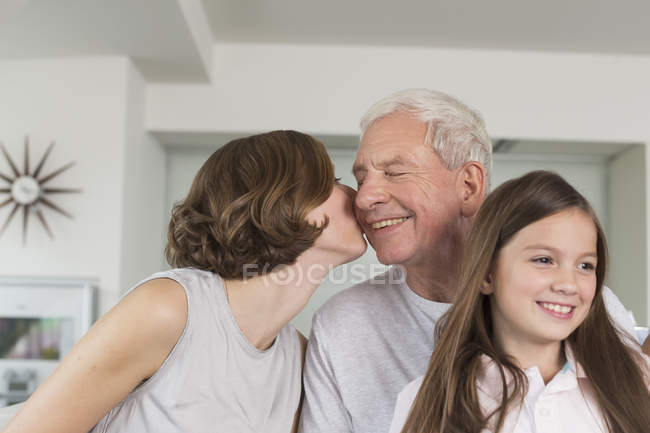 Adult daughter kissing father — Stock Photo