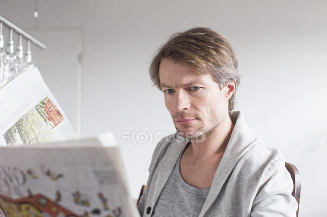 Mature man reading newspaper — Stock Photo