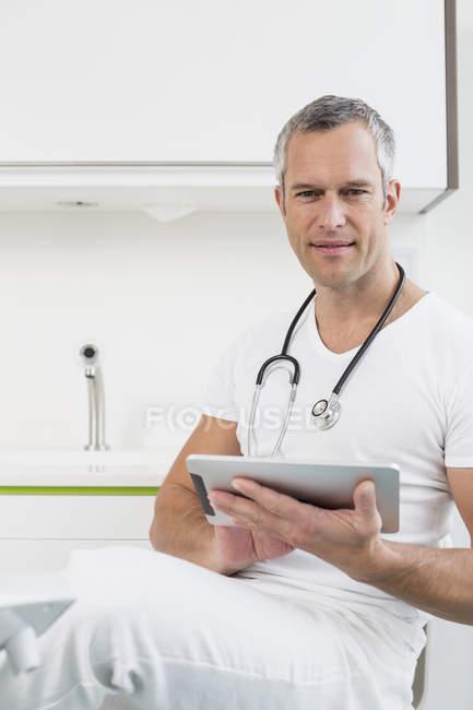 Médico en el hospital con tableta digital - foto de stock