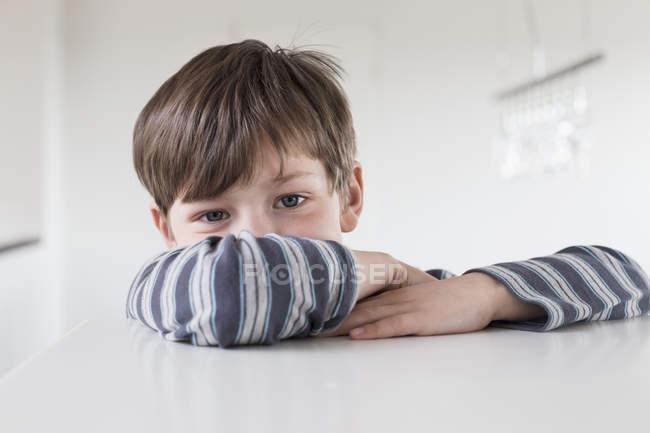Menino inclinado na mesa — Fotografia de Stock