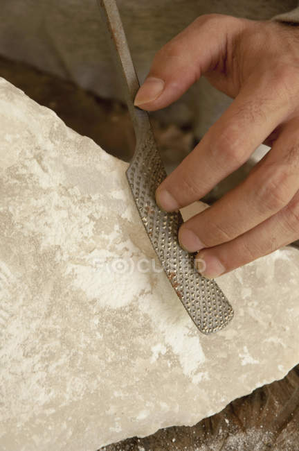 Mature man carving soapstone — Stock Photo