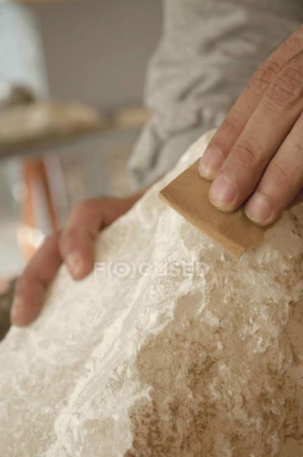 Mature man polishing soapstone — Stock Photo