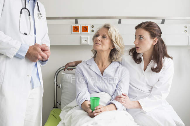 Woman and doctor sitting on bed — Stock Photo