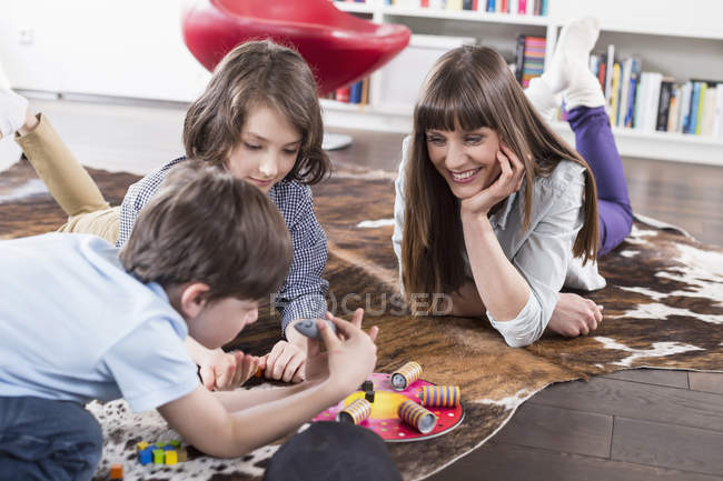 Mother playing board game with children — Stock Photo