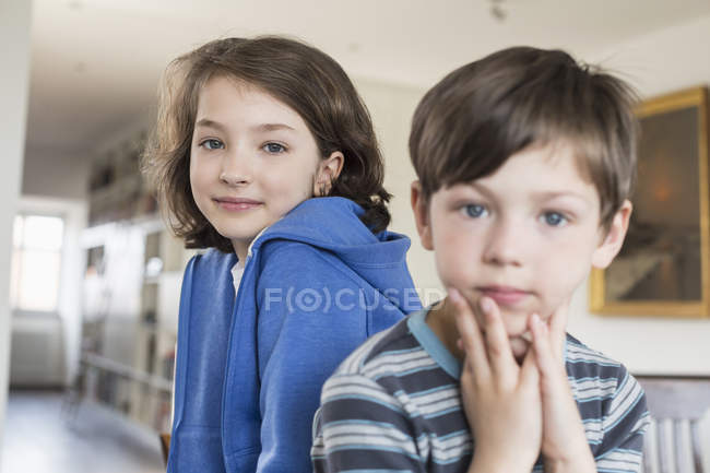 Hermana y hermano mirando a la cámara - foto de stock