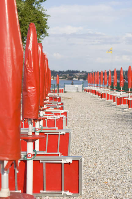 Empty beach with closed umbrellas and tables — Stock Photo