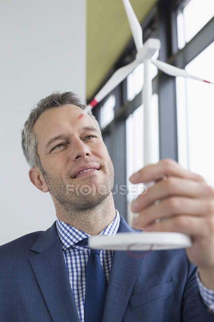 Businessman holding wind power model — Stock Photo