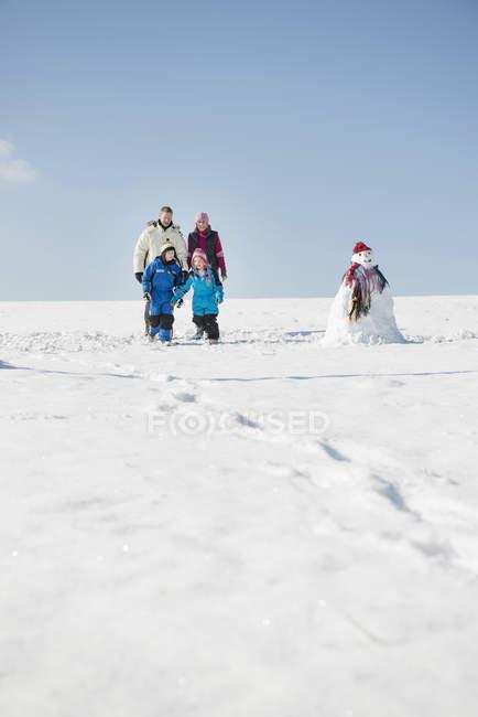 Семья стоит на снегу рядом со снеговиком — стоковое фото