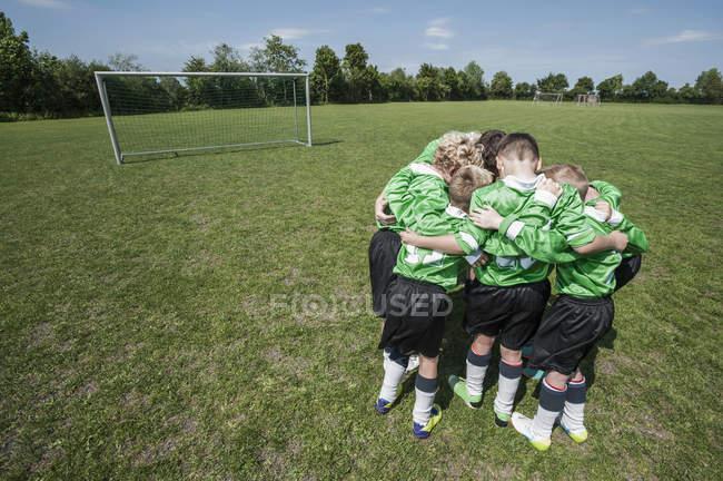 Squadra di calcio junior in cerchio huddle — Foto stock