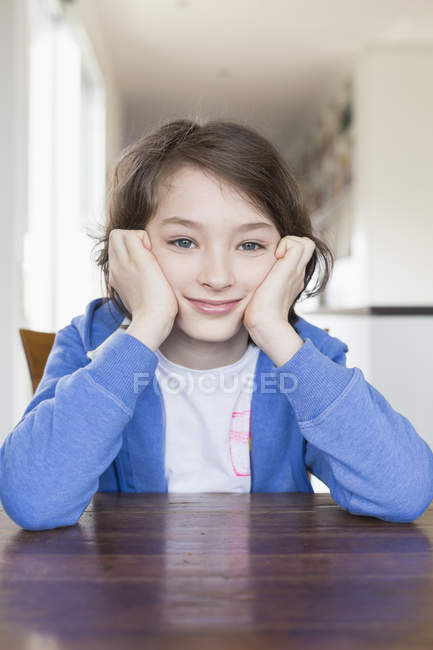 Girl Sitting At Table With Head In Hands Front View Indoor Stock Photo 126753198