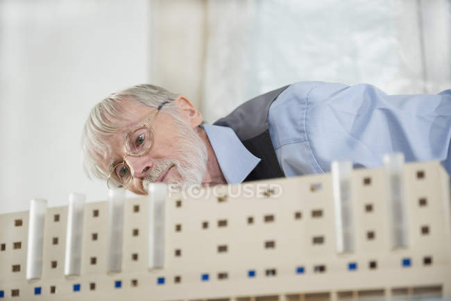 Architect looking at architectural model — Stock Photo