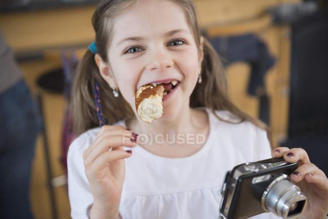 Девушка с без зубов едят булочке — стоковое фото