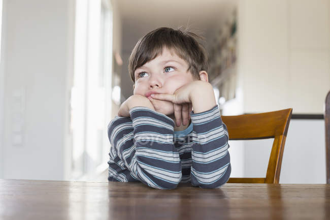 Boy leaning on wooden table and daydreaming — Stock Photo