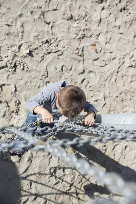 Small boy climbing chain — Stock Photo