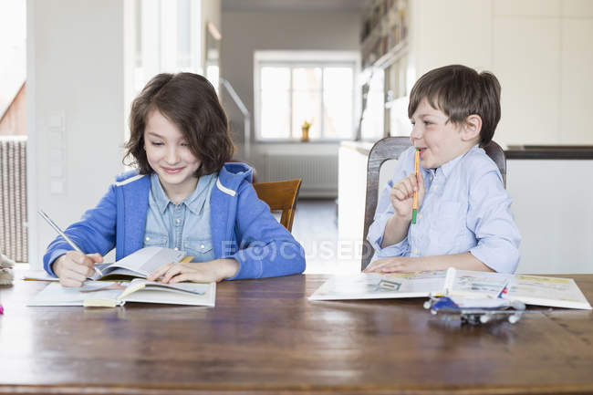 Girl and boy doing homework together — Stock Photo