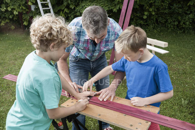 Father and sons working with wood — Stock Photo