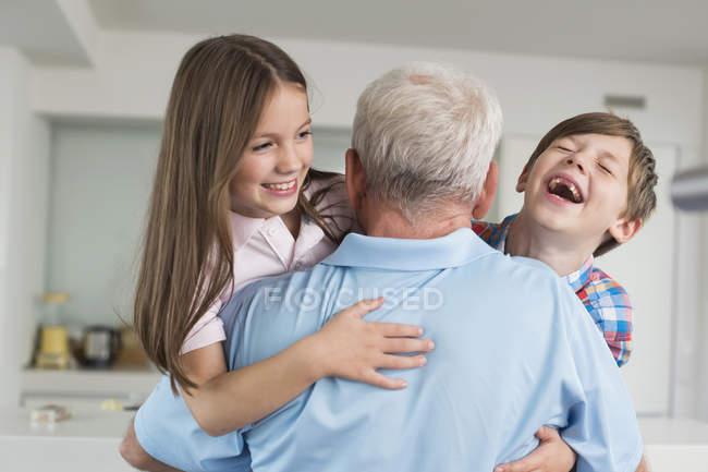 Grandfather hugging happy grandchildren — Stock Photo