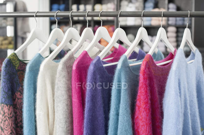 Handcrafted woolen clothes on hangers — Stock Photo